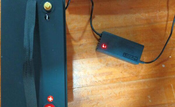 購入時に付属したリン酸鉄リチウムイオンバッテリー専用充電器、充電中はLEDが赤点灯